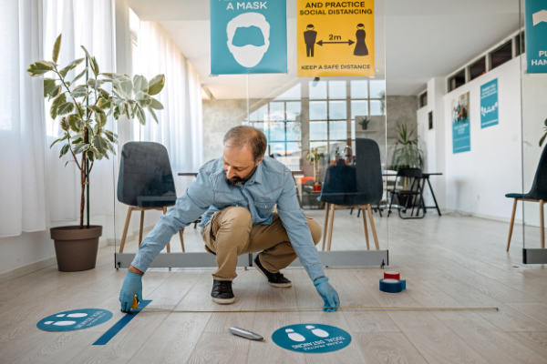Staff member places social distancing stickers on the floor