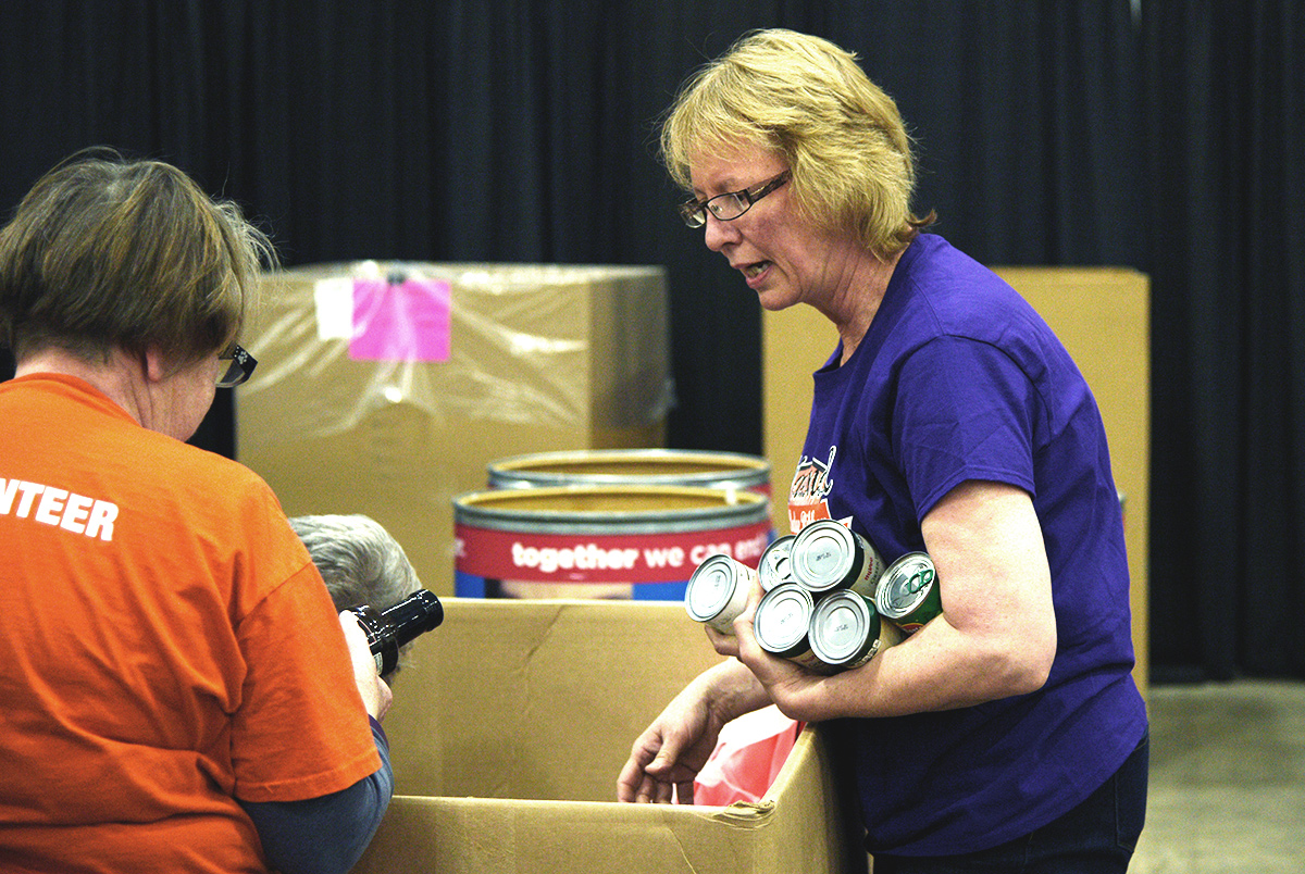 pc/nametag team members sort canned goods for Second Harvest Foodbank