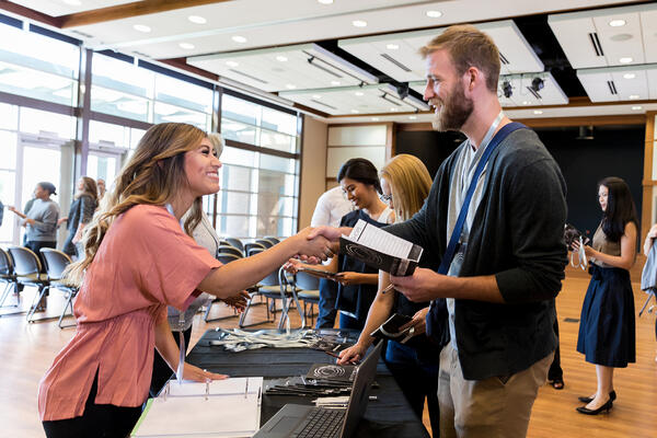 Registration Booth Worker Helps Conference Attendee