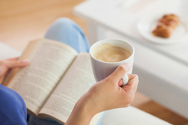 Woman reading a team book club book with coffee