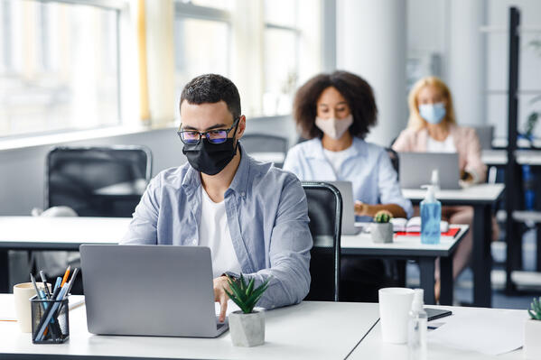 Employees practice social distancing and wear masks