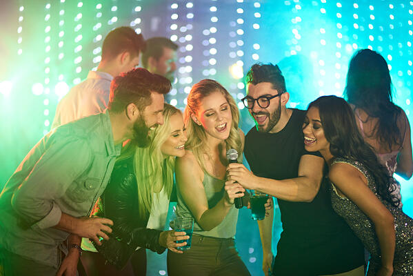 young adults sign karaoke at a music themed party